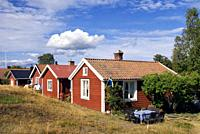 Traditional red painted houses in the Swedish village Holick on the Hornslandet peninsula at the Bothnian Gulf.