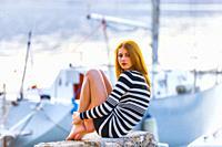Teen girl on seaside tucked legs barefeet