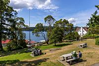 People sitting in a park above the ferry dock in Orcas Village on Orcas Island in the San Juan Islands in Washington State, United States.