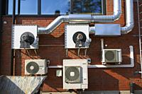 Ventilation and air conditioner machinery on building wall exterior.