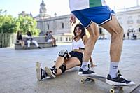 Two young people riding on skateboards in the city.
