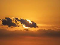 Sun behind small clouds in orange sky near sunse.