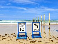 Two beach driving traffic sign sitting on wet sand with Atlantic Ocean waves in the background and seaweed in the forground and whispy cirrus clouds i...