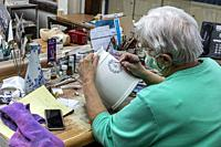 Holland, Michigan - An artist paints Delftware at the De Klomp Wooden Shoe and Delft Factory, part of the Veldheer Tulip Farm. The city's Dutch herita...