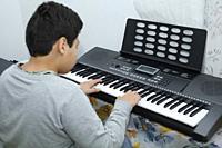 Boy playing a smart piano.