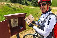 Cyclist stamping a passport on the Otago Central Rail Trail, Otago, South Island, New Zealand.