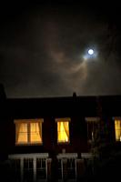 Blurred House Facade with Lights on Under Moonlight.