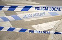 Municipal Police tape close to crosswalk. Banner letters in spanish languaje.