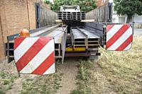 Building materials truck loaded with steel beams. Oversize load length restrictions concept.