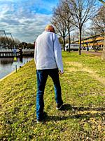 Kaatsheuvel, Netherlands. mature adult male suffering from Early Dimentia walking down a canal river bank.