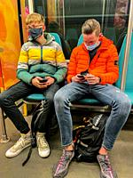 Rotterdam, Netherlands. Two young adult males commuting by subway while constantly checking their smartphones.