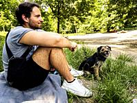 Berlin, Germany. Caucasian Male playing with his little dog inside Volksprak Hasenenheide Doggy Playground.