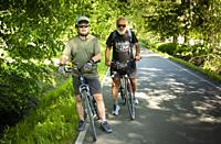 Two men bicycle on the Poco trail in Port Coquitlam, BC, Canada.