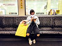Berlin-Mitte, Germany. Young, Asian woman with shopping bags and smartphone riding the U-Bahn / S-Bahn during her commute home.