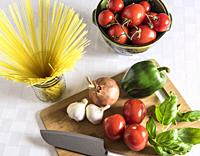 Italian ingredients displayed on a cutting board with chef knife.