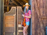 Teen girl violin player American West saloon.