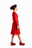 woman with walking in a red knit dress on white background.