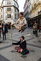 Prague, Czech Republic, Europe - Passersby gaze in wonder at the trick of what appears to be a floating street performer (busker) in a pedestrian zone...