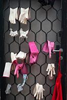 Singapore, Republic of Singapore, Asia - Damp rubber gloves hang for drying at a gate in the city district of Chinatown.