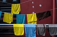 Singapore, Republic of Singapore, Asia - Damp towels hang for drying on a clothesline in the city district of Chinatown.