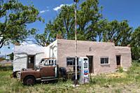 La Jara, Colorado, A rusty, old pickup truck, parked in front of an old Chevron gas station, in southern Colorado.