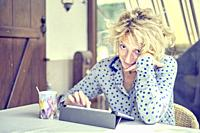 Portrait of a blond hair young mature caucasian woman with a notepad computer indoor at home working with a funny gesture. Quarantine concept. Working...