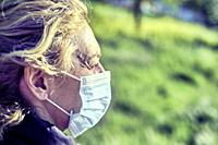 Portrait of a young mature caucasian blonde woman outdoor with face mask. Pandemia concept.