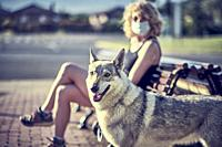 Young mature caucasian woman outdoor sitting on a park bench with face mask and her wolf dog. Pandemic concept.