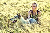 portrait of a young mature caucasian woman with her wolf dog outdoor in a cereal farmland landscape. Lifestyle concept.