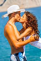 Adolescent teen couple are kissing on the beach