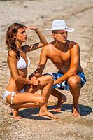 Muscular boy slender girl young couple on the beach are looking away