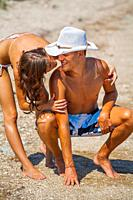Muscular boy slender girl young couple on the beach going to kiss
