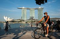 Singapore, Republic of Singapore, Asia - A man wearing a protective face mask cycles on his bike along the waterfront by the Singapore River during th...