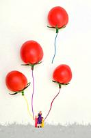 Miniature Family Playing With Balloon From Red Cherry Tomatoes.