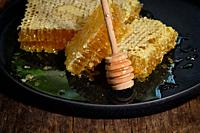 Closeup Honeycomb and honey dipper on wooden table.