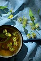Cup with linden tea and flowers and natural light.