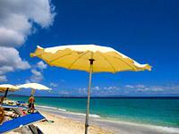 Yellow beach umbrella at Platamona beach in summer 2021, Gulf of Asinara, Sassari, Sardinia, Italy, Europe.