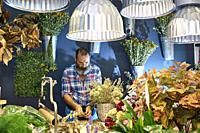 A florist taking care of various flowers and bouquets in his shop.