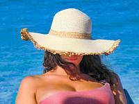 Close up of a beautiful girl with straw hat on Platamona beach in summer 2021, Gulf of Asinara, Sassari, Sardinia, Italy, Europe.