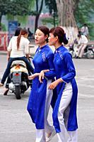 Vietnamese woman in traditional dress walking in the street, Hanoi. Vietnam