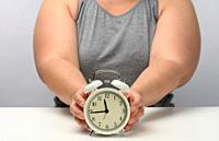 plump woman sits at a table and holds a round white alarm clock. The concept of fractional nutrition, time to lose weight, adherence to sleep.