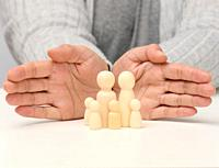 wooden figurines of men, a family guarded by two female hands. Help, life insurance, safety.