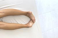 Crossed feet on a bed.