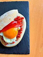 Tapa made of picadillo, fried egg and red pepper in bread. Spain.