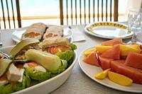 salad with salmon and tuna fruit and meat loaf on a table on the porch of a villa with a pool