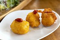 Three round Cod fish croquettes on dish with jam on top
