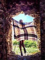 Young woman with a flying scarf back-view from within a tunnel balancing on one leg