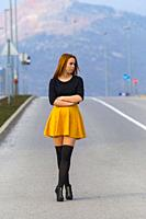 Sad teen girl is standing alone on the empty road looking away
