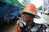 Yangon, Myanmar, Asia - A rickshaw driver takes a break and smokes a cigarette with pleasure.