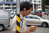 Singapore, Republic of Singapore, Asia - A man smokes a cigarette in Chinatown.
